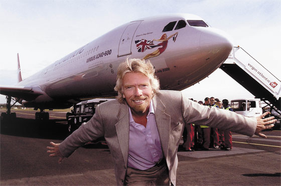 Richard Branson in a take-off pose with one of his Virgin Airlines plane in the background